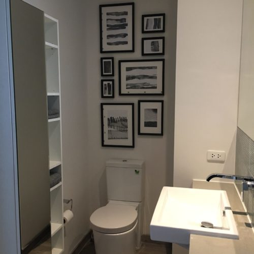 contemporary bathroom with pictures in black frames