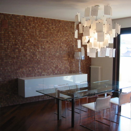 dining room with glass table and bricks wall