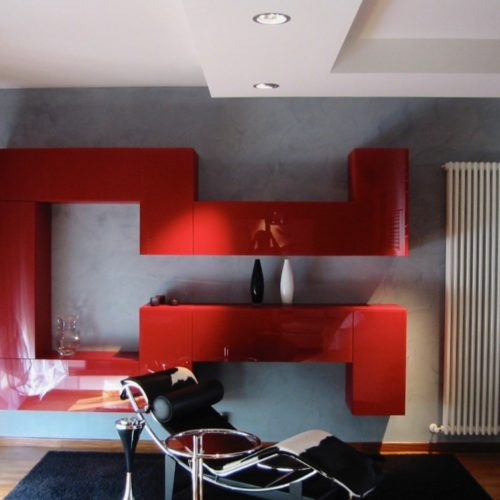 contemporary living room with red cabinets and designer chair